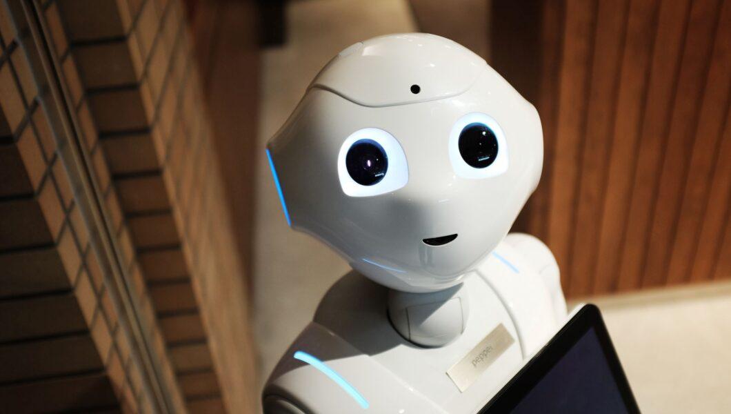 biały humanoidalny robot patrzy w obiektyw);