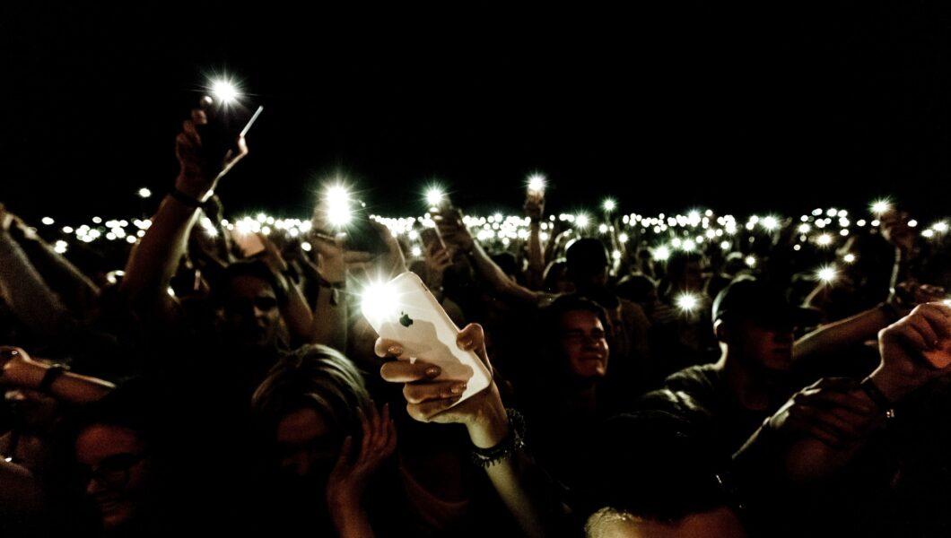 ciemna sala koncertowa i rozświetlający ją błys setek lamp od telefonów);