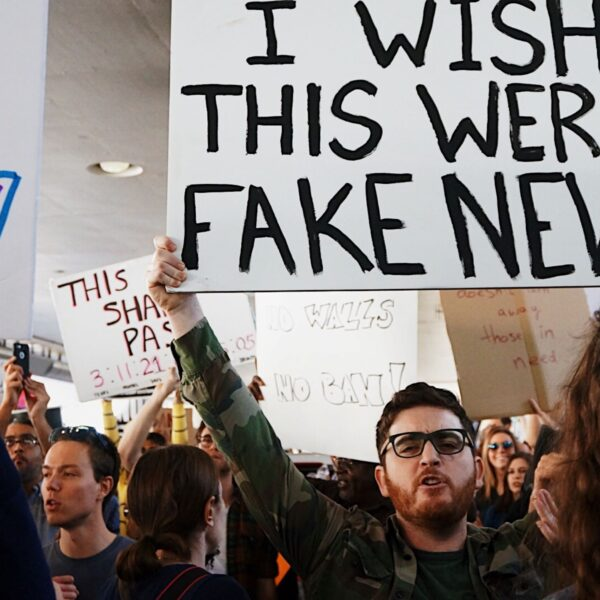 zdjęcie protestującego tłumu, mężczyzna z brodą trzyma transparent);